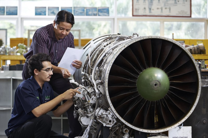 A student is undergoing practical training under the supervision of lecturer in the aircraft hangar.