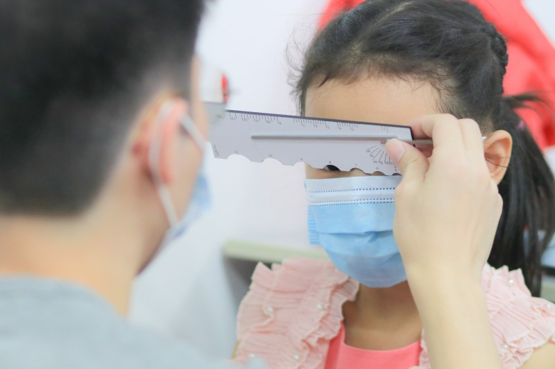 A student is taking facial measurement of a child in his dispensing practice
