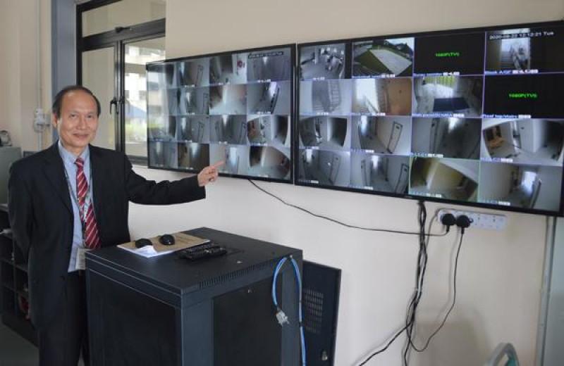 廖锦兴展示保安室内的监控,校内各处皆有装置闭路电视,保障学生安全。