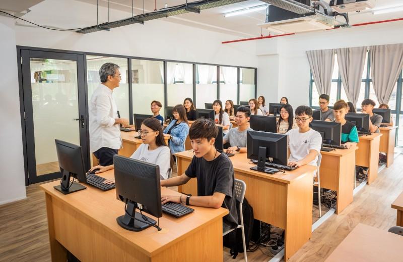 在舒适的电脑室排版编辑的学生们。