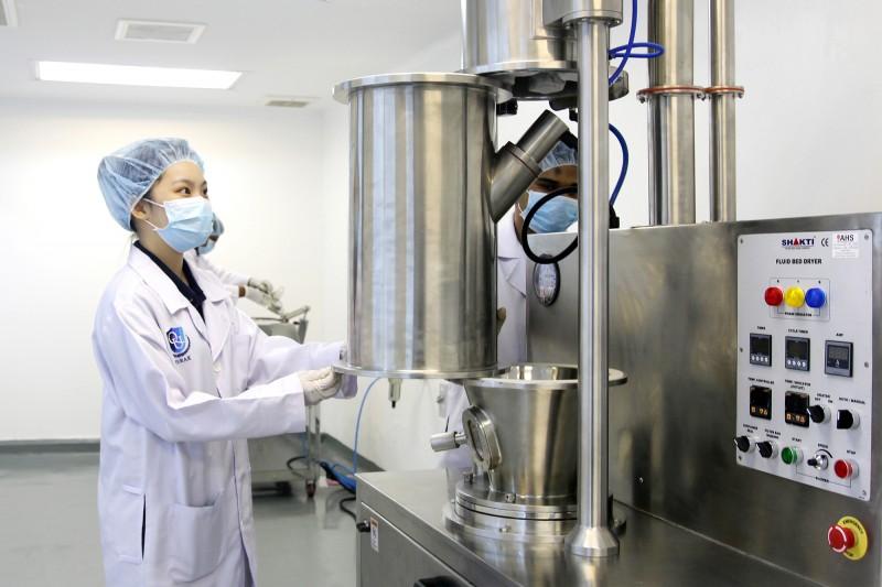 药剂系学生正在检测制造药物生产线流程。